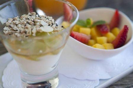 Copo com Iogurte caseiro com granola de quinoa e vasilha com frutas cortadas ao lado
