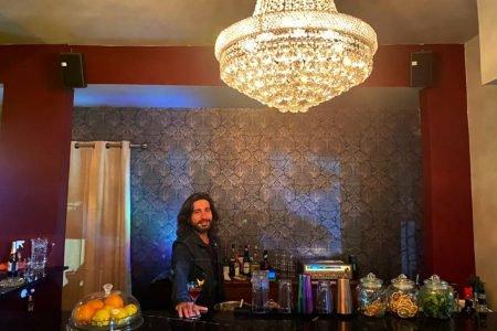 Homem segura taça com drinque sobre mesa de bar