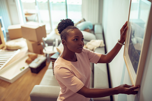mulher colocando quadro na parede em casa cheia de caixas