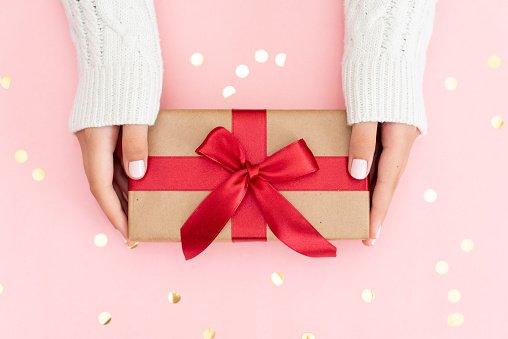 mãos segurando embalagem de presente