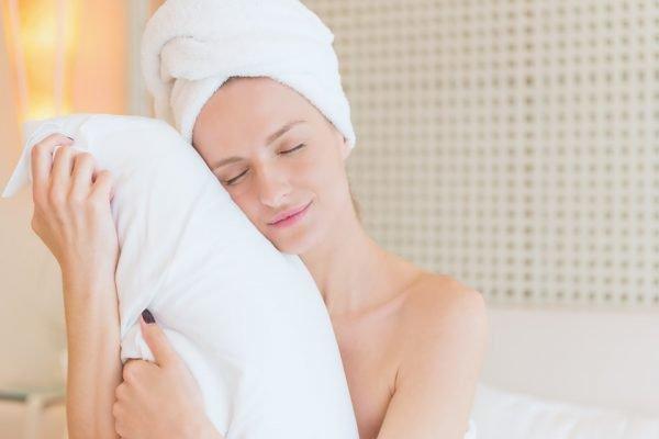 mulher com toalha no cabelo prestes a dormir
