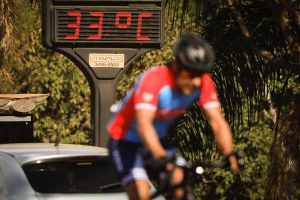 Ciclista faz esporte próximo ao termometro marcando 33 graus