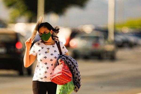 mulher se protege do calor na area central de Brasilia