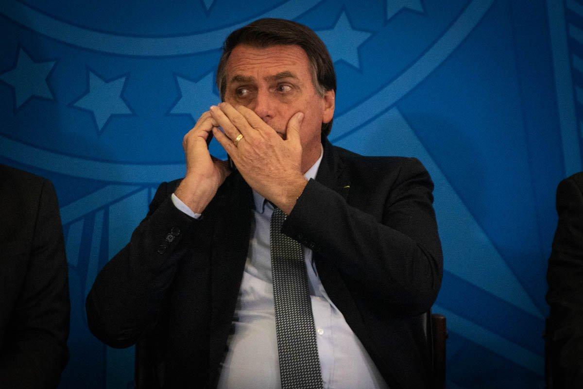 Presidente Jair Bolsonaro conversa ao celular no planalto